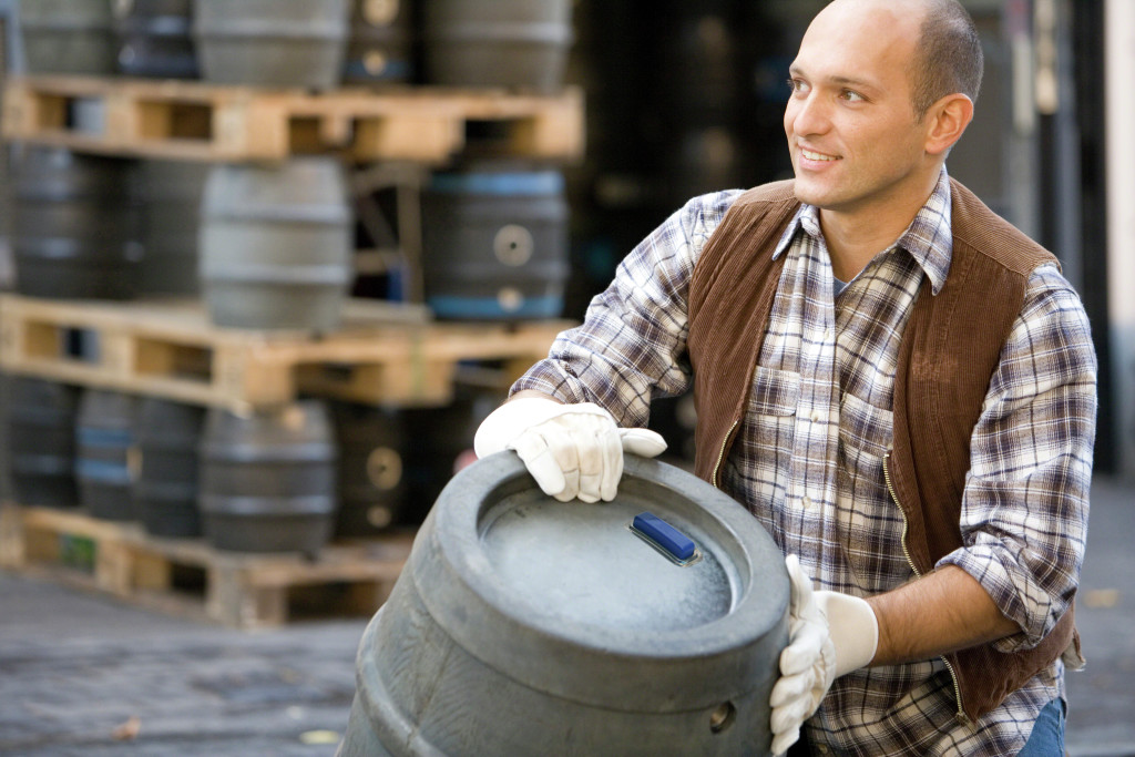 Worker moving keg with keg tag